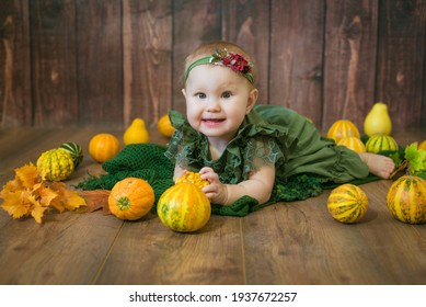Cute little girl up to 1 year old in a green cute dress and a floral wreath with small yellow and orange pumpkins on a brown wooden background