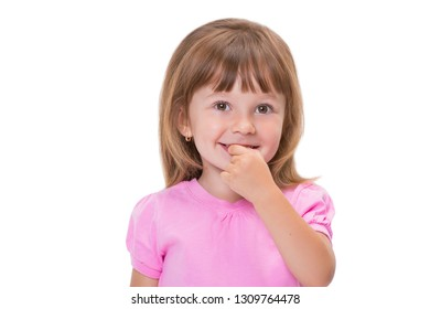 Cute little girl 3 year old in pink t-shirt holds fingers in mouth or bites nails isolated on white background. Bad childhood habits