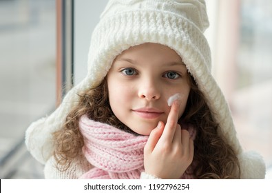 Cute little girl applying protecting cream to her face. Winter skin protection concept.   Portrait of smiling kid in winter clothes.