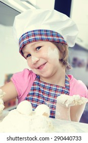 Cute little girl in apron baking cookies at home kitchen