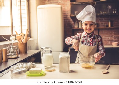 Cute little girl in apron and chef hat is whisking eggs in the bowl, looking at camera and smiling while preparing dough for baking