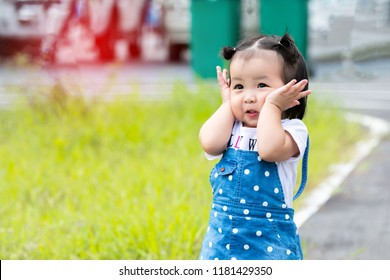 Cute little girl Asian happiness shot outdoors on lawn, 1-2 year old