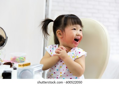 A cute little girl asian with mess lipstick all over face