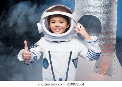 Cute little girl in astronaut costume showing thumb up and smiling at camera