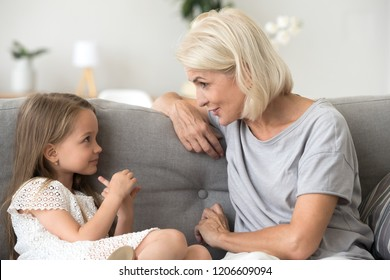 Cute little girl and attentive grandmother sit on couch at home having casual conversation, happy granny talk with granddaughter having fun, grandma and grandchild spend time together communicating