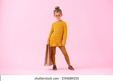Cute little girl in autumn clothes and with shopping bag on color background