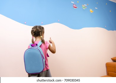 Cute little girl with backpack, back view, thumbs up. Preschool concept