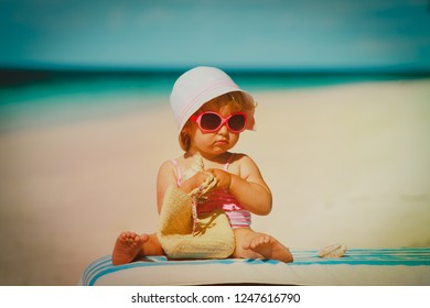 cute little girl with bag on tropical beach vacation