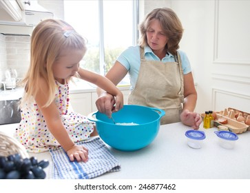 Cute little girl baking with her grandmother at home