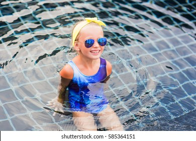 cute little girl with a bandage on his head in the sun-colored glasses in the pool floating on a summer day.