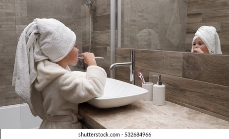 Cute little girl in a bath towel on the head and a bathrobe cleaning teeth in the bathroom against the mirror