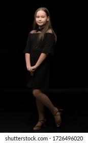 Cute little girl in a beautiful dress on a black background.