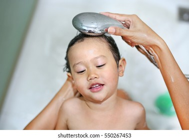 cute little girl is being bathed and shampooed by her mother