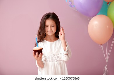 Cute little girl with Birthday cake making a wish on color background
