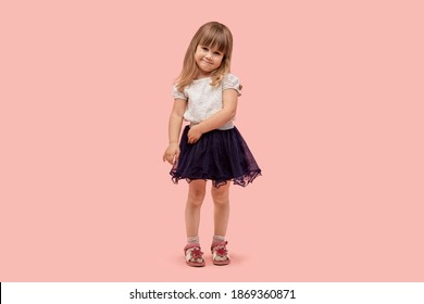 Cute little girl in a black skirt and a full-length white t-shirt. Pink background.