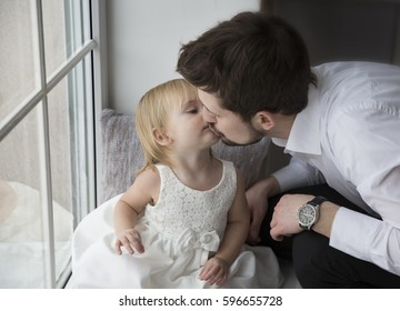 Cute little girl with blond hairin white dress with she's father in black suit interior.