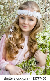 cute, little girl blonde little princess with amazing eyes, standing in a garden on a background of white flowers, wreath on his head and the hands holding white flowers, the spring and holy communion