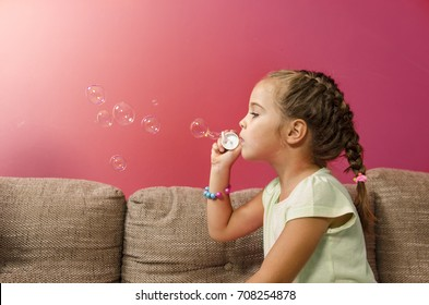 Cute little girl blowing bubbles indoors, copy space , red wall background