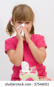 cute, little girl blowing out her nose, on white