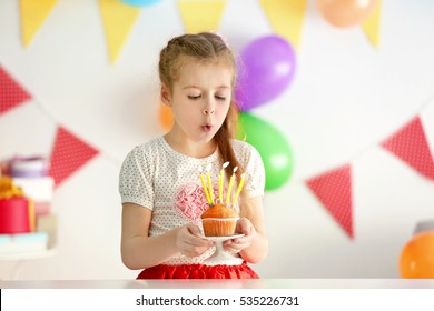Cute little girl blowing out candles on birthday cake at home