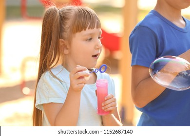 Cute little girl blowing soap bubbles outdoors