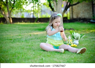 Cute little girl is blowing a soap bubbles on Easter