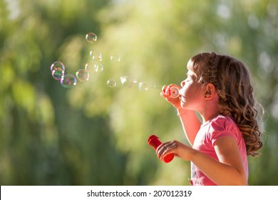 Cute little girl with blowing soap bubbles  in park