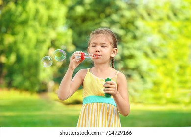 Cute little girl blowing soap bubbles outdoors