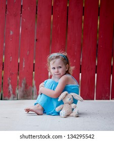 Cute little girl with blue eyes wearing blue dress sitting on concrete with stuffed bunny in front of red fence