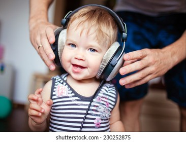 cute little girl with blue eyes in the headphones, smiling