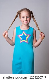 Cute little girl in a blue jumpsuite with a colorful star on a chest holding her tails and looking happy