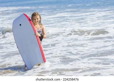Cute little girl boogie boarding in the ocean