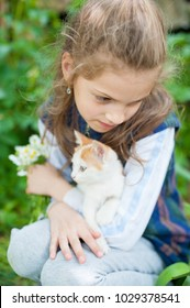 cute little girl with a bouquet of flowers and a kitten on her hands