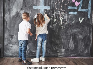 Cute little girl and boy drawing with crayon color on the wall. Works of child. Cute pupil writing on chalkboard.