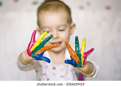 Cute little girl or boy hands painted in colorful paints. Close up portrait of a child with painted hands.