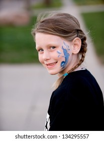 Cute little girl in braids with her face painted looking over her shoulder smiling