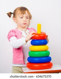 Cute little girl build stacking cups, girl play with stacking cups