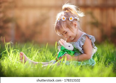 Cute little girl with a bunny rabbit has a easter at green grass background