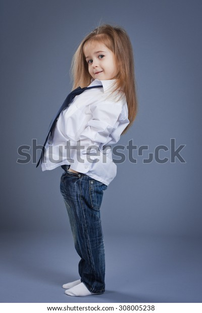 Cute little girl in a business suit and tie, studio