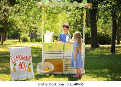 Cute little girl buying homemade lemonade in park