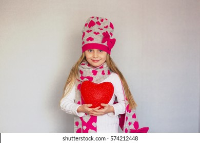 cute little girl in a cap and a scarf with a heart holding a red heart. Valentine's day holiday.