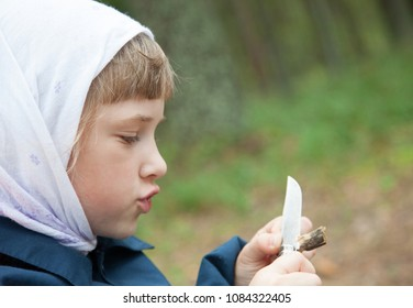 Cute little girl carefully carving a wooden toy outdoors