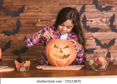 Cute little girl is carving a pumpkin and smiling, on background decorated for Halloween