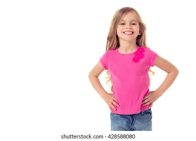 Cute little girl in casual clothes is looking at camera and smiling while standing akimbo, isolated on a white background
