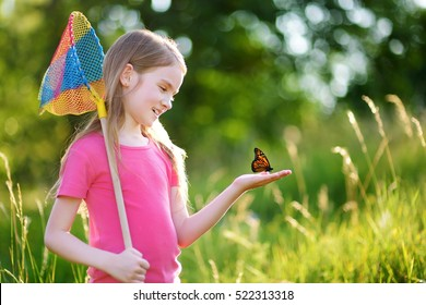Cute little girl catching butterflies and bugs with her scoop-net on beautiful sunny summer day