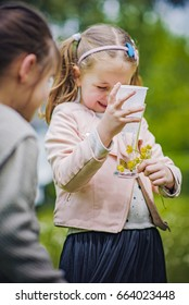 Cute little girl caught a butterfly in a glass jar, having fun on a bright summer day
