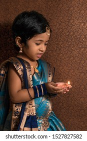 Cute little girl celebrating diwali or Deepawali or Terracotta oil lamp on Diwali festival