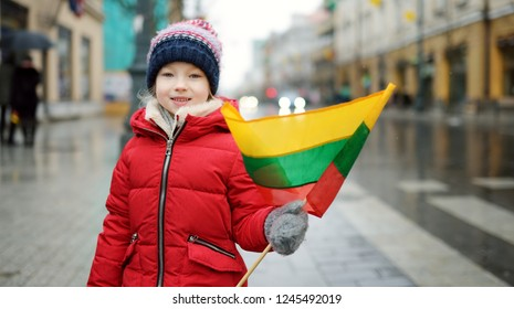 Cute little girl celebrating Lithuanian Independence Day holding tricolor Lithuanian flag in Vilnius, Lithuania