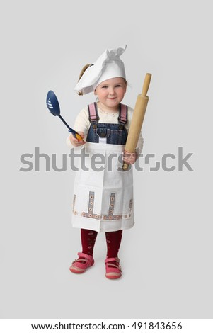ab47a0c6c02 Cute little girl in chef hat and apron stands with plunger and ladle in  hands and