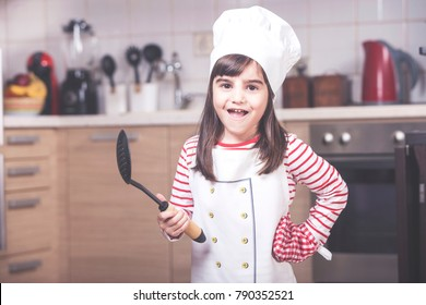 Cute little girl chef posing in the kitchen